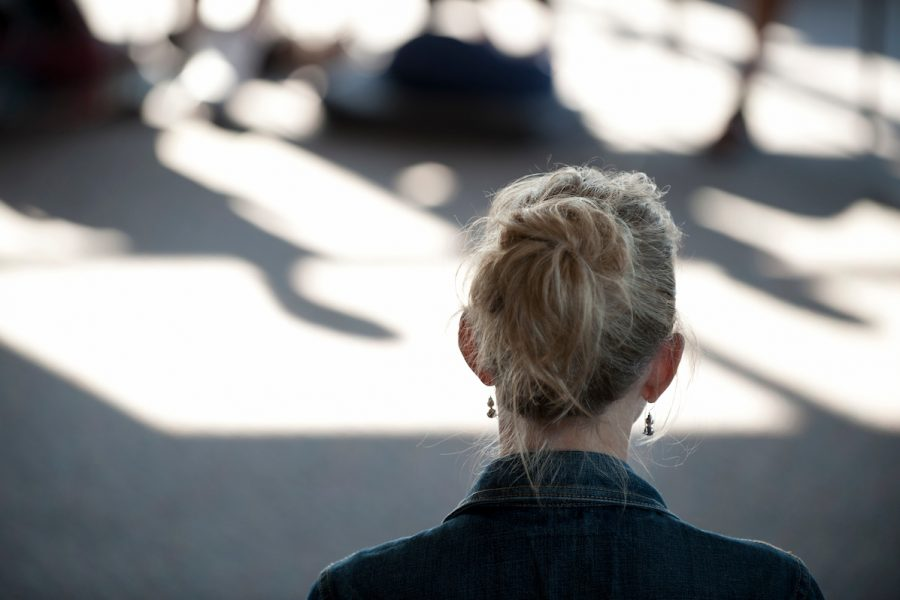 back of a woman's head during meditation in a sunlit room.