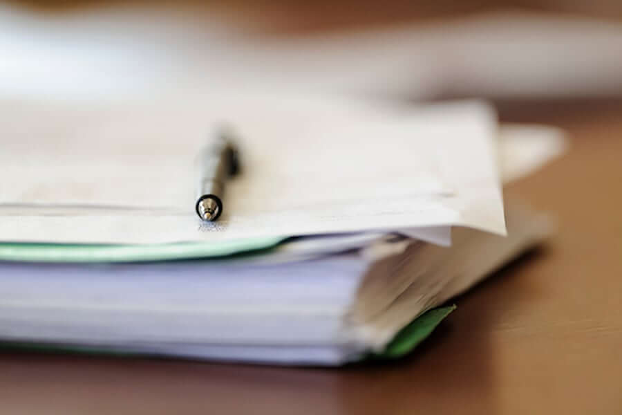 A pen rests on a stack of papers.