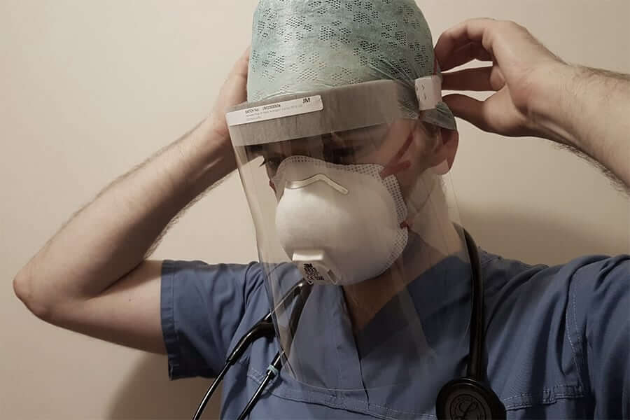 Health care worker putting on face shield